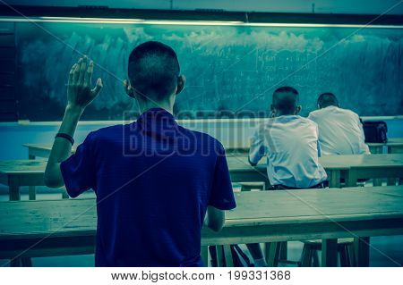 the students Raised hands in classroom at School between classmate education concept