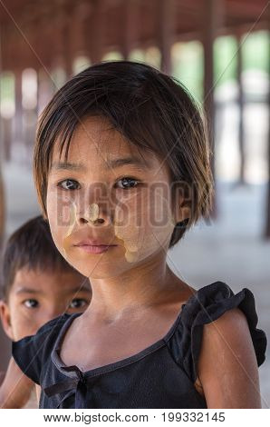 MANDALAY MYANMAR - MARCH 10 : Unidentified Burmese girl with traditional thanaka on her face on March 10 2016 in Mandalay Myanmar.Thanaka is a yellowish-white cosmetic paste made from ground bark