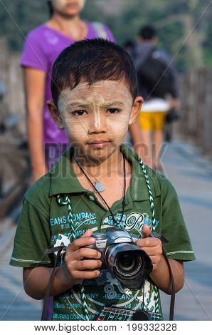 MANDALAY MYANMAR - MARCH 13 : Unidentified Burmese boy holding the camera at the ubein bridge on March 13 2016 in Mandalay Myanmar. The U-Bein bridge is the longest teak bridge in the world 1.2km length.