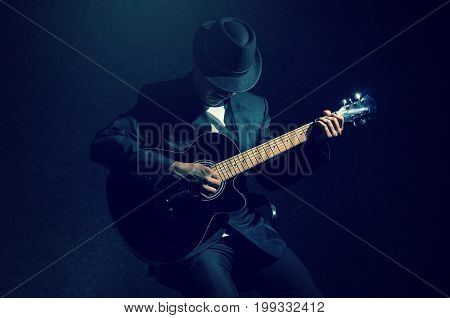 Musician playing the guitar on black background music concept