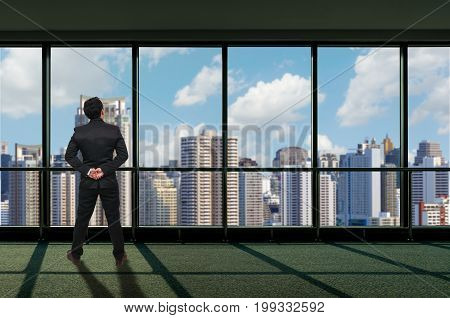 Back side of Businessman looking megalopolis through window Business concept