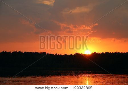 Storm clouds and sunset on lake and forest silhouette background. Nature summer sunlight wallpaper