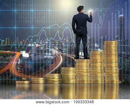 Businessman standing over the stack of gold coins and drawing over the Trading graph on the cityscape background Business financial concept,