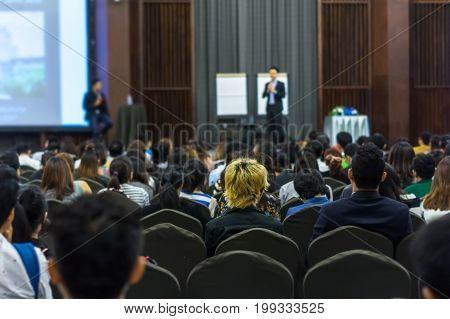 Speaker on the stage with Rear view of Audience in the conference hall or seminar meeting business and education concept