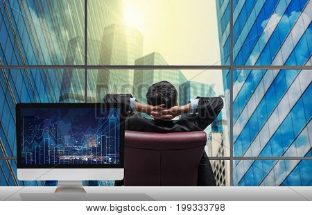 Back side of sitting businessman who is looking at citiy out off windows glass with Computer set show Trading graph on the cityscape and world map background on the table Business financial concept,