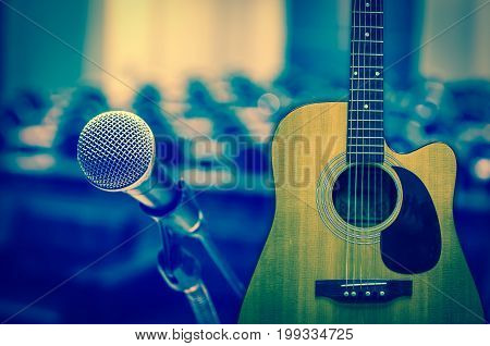 Guitar and Microphone over the Abstract blurred photo of concert or conference hall or seminar room background