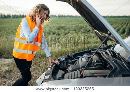 Girl in reflecting vest with phone, broken car