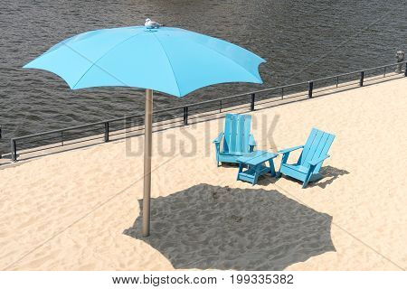 Two Blue Chairs With Parasol On A Beach