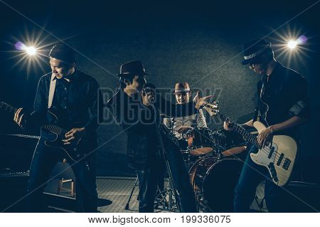 Musician band hand holding the microphone and singing a song and playing music instrument with Fellow band musicians on black background with spot light and lens flare musical concept