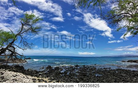 Lava Rock and Coral with Spray of crashing waves in beach tide pools at Maluaka Beach and Kihei Maui with sky and clouds