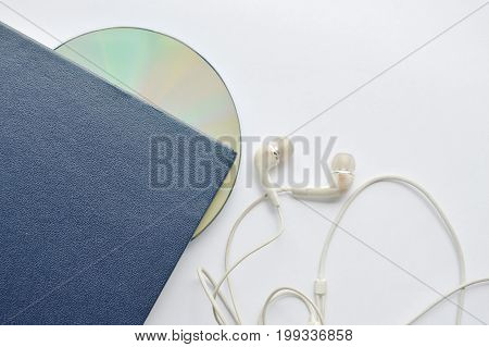 book and CD- rom with earphones on white background