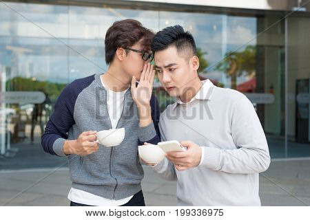 Closeup Portrait Of Guy Whispering Into Man's Ear Telling Him Something Secret
