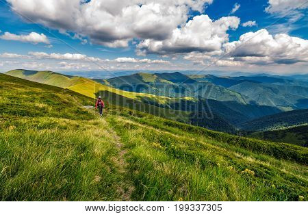 Woman Hike Through Grassy Slope In Mountains