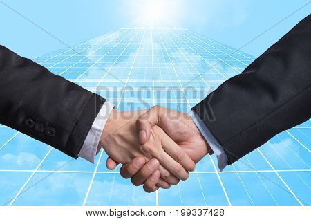 Hand shake between a businessman on Modern glass building background