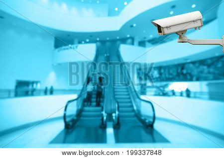 Security camera monitoring the Abstract blurred photo of escalator with bokeh background blue color tone