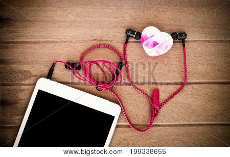 Portable audio earphones with tablets and heart soap on wood background