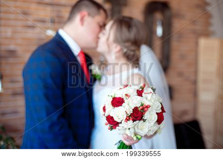 wedding couple kissing holding bouquet in front of themselves