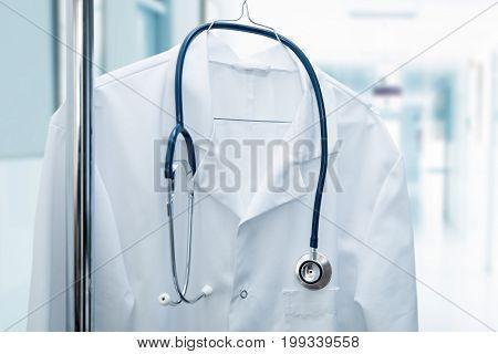 job vacancy - white doctor coat on hanger in hospital hallway