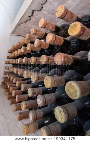 Many bottles - lie one above the other. Bottle with a wooden stopper. Bottle necks at the viewer.