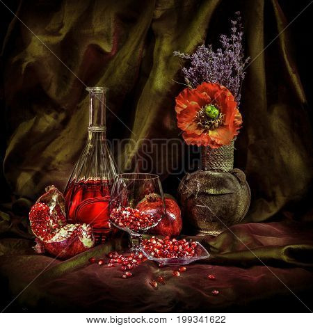 Beautiful still life image of pomegranate juice, vintage vase with a flower. Brushed disclosed fruit garnet grains in the glass. Photographed light brush technique.