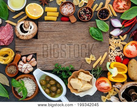 Italian Food Cooking Ingredients On Dark Stone Background With Cutting Board Flat Lay And Copy Space
