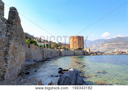 Kizil (red) tower with alanya fortress with alanya city background with mountains