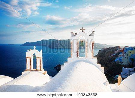 white church belfries and volcano caldera with sea landscape, beautiful details of Santorini island, Greece, retro toned