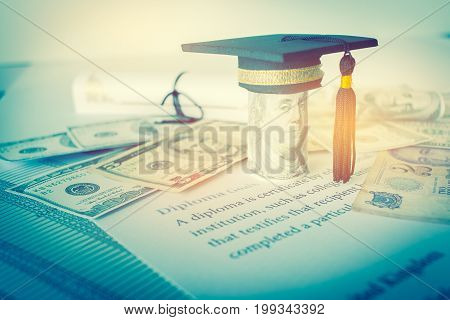 Concept of graduation black cap on roll up Dollars bill with diploma or certificate on letters foreign money US dollars Singapore. Education of competition on abroad program in famous institution.