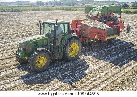 Badajoz Spain - August 12 2017: Tractor pulling an onion harvester. Badajoz Guadiana meadows Spain