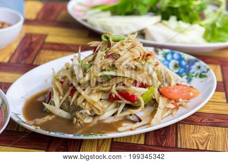 SOM-TAM Thai delicious raw papaya salad with unique taste hot and spicy this dish with tomato and crab. Papaya salad with red chili.