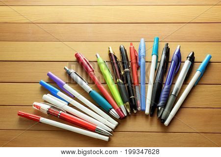 Row of Ballpoint Pens on Wooden Background