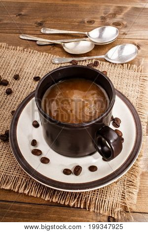 milk coffee in a cup on a saucer with beans and spoon