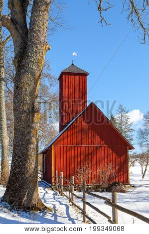 Old post station in small village. Red woooden building with tower. Scandinavian style.