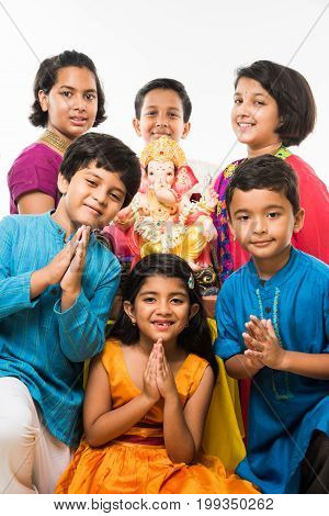 Indian Cute kids holding statue of Lord Ganesha or Ganapati on Ganesh festival or chaturthi, welcoming god. Asian small boys and girls with Lord Ganesha, Standing over white background