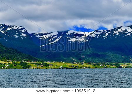 View over water, little houses at the foot of snow Mountains. Cloudy sky, narrow strip of ground in sun light. Egersund, Norway
