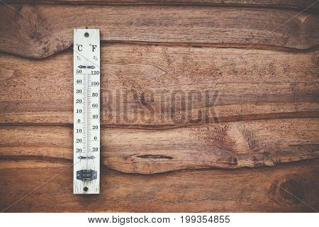 Wood thermometer calibrated in degrees celsius on the wooden wall concept of world hot and weather.