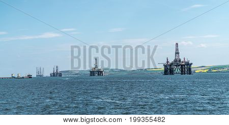 Panorama of a row of decommissioned oil rigs from the North Sea in the Cromarty Firth Scotland