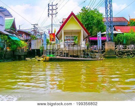 Bangkok, Thailand - June 30, 2008: Wooden slums on stilts on the riverside of Chao Praya River in Bangkok, Thailand