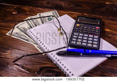 Notepad, Pen, Calculator And Dollar Bills On Wooden Table
