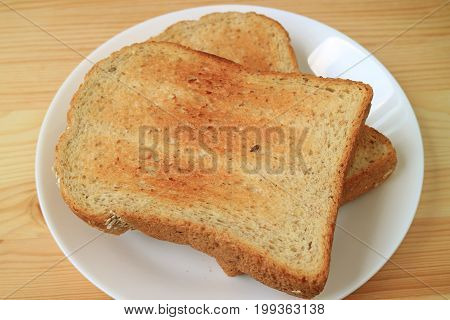 Two pieces of whole wheat toast served on ceramic white plate on wooden table
