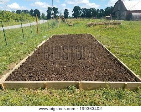 Raised bed in garden filled with compost ready to plant
