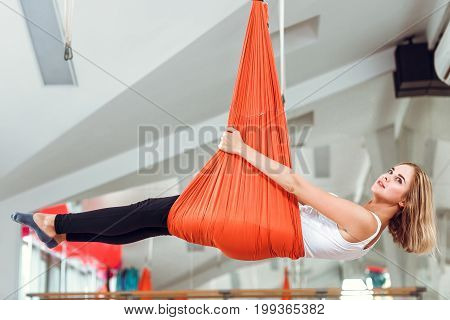 Fly yoga. Young woman practices anti-gravity yoga with a hammock .