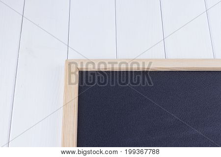Old blank vintage school slate or chalkboard lying on an old rustic wooden background