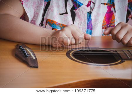Close-up child playing guitar. Concept of liftstyle learning hobby musician dream and imagination.