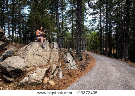 Young teenage girl sitting on a rock and reading a book at Troodos forest in Cyprus