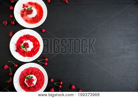 Panna cotta with fruit syrup and tasty berries in a plates on a dark table. Flat lay. Top view