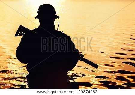 Silhouette of special forces with rifle in action during river raid in the jungle waist deep in the water. Front view, half length