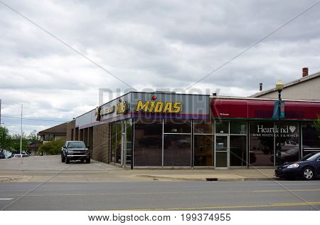 CADILLAC, MICHIGAN / UNITED STATES - MAY 31, 2017:  Midas offers automobile service and repair, on Mitchell Street in Downtown Cadillac.