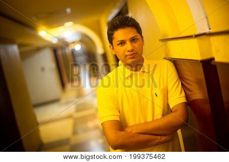 Portrait of young businessman standing in seminar hall.