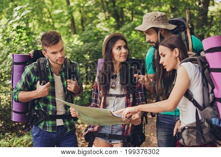 Four Tourists Got Lost In The Forest, Holding Map, Trying To Find The Way, Disscus It, All Having Ba